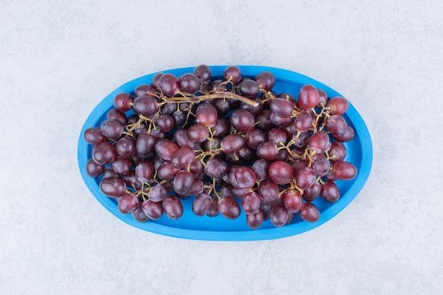 흰색 바탕에 파란색 접시에 신선한 달콤한 포도. 고품질 사진