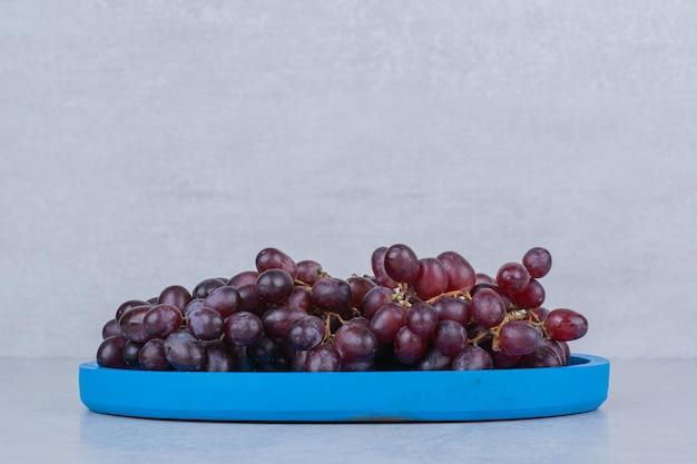 Свежий сладкий виноград в голубой тарелке на белом фоне. фото высокого качества