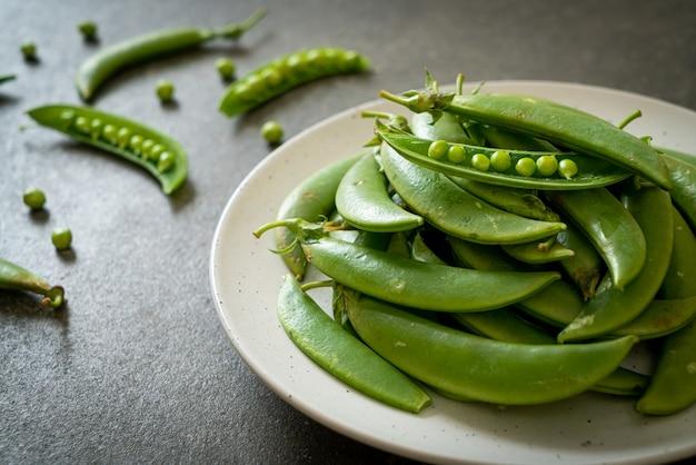 Fresh sweet green peas on white plate