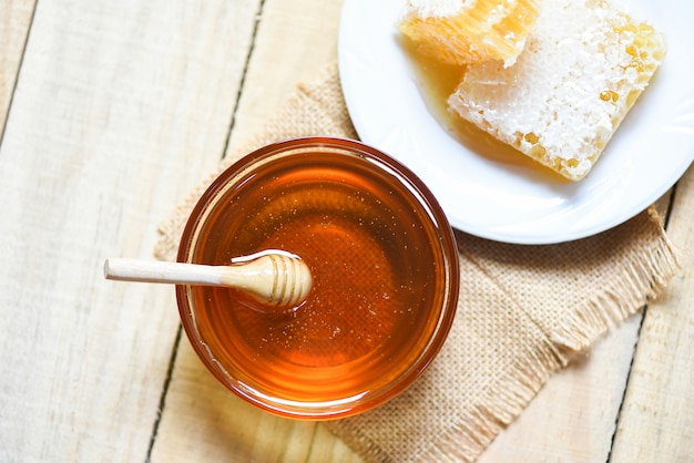 Fresh sweet honey in jar with wooden dipper and honeycomb on plate on wood table