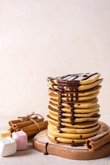 Fresh sweet pancakes with chocolate jam, cinnamon sticks and marshmallows