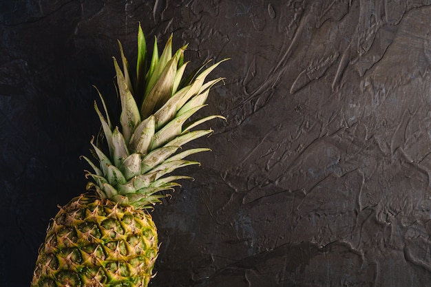 Fresh sweet pineapple on dark black textured surface, top view copy space