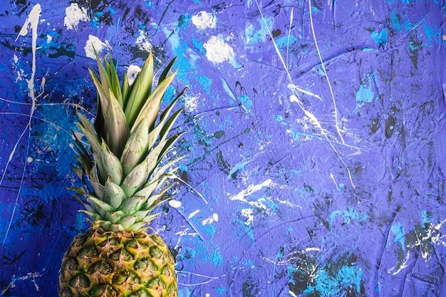 青い織り目加工の表面、トップビューコピースペースに新鮮な甘いパイナップル