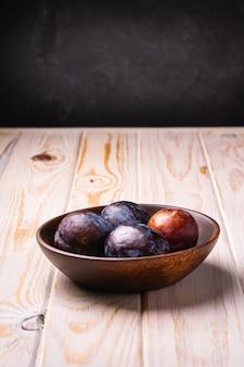 갈색 나무 그릇에 신선한 달콤한 자두 과일