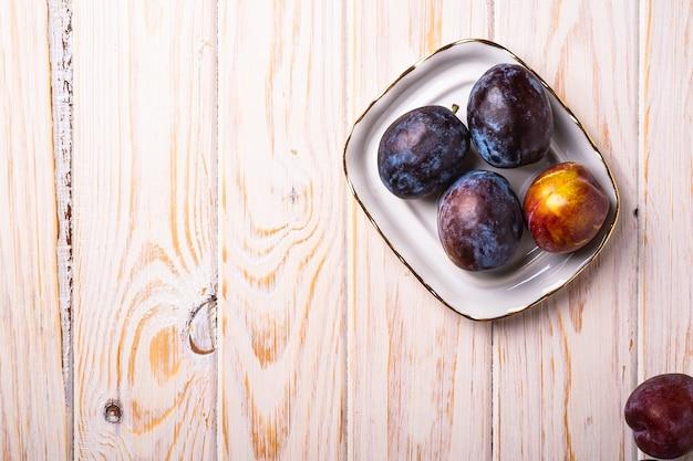 나무 테이블 표면에 흰색 접시에 신선한 달콤한 매실 과일, 상위 뷰 복사 공간