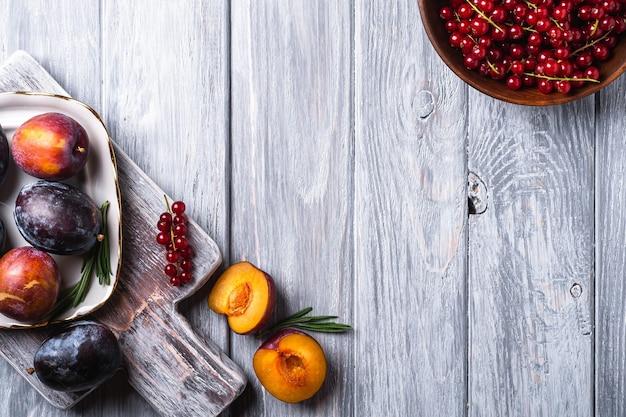 Свежие сладкие плоды сливы целиком и нарезанные в тарелке с листьями розмарина на старой разделочной доске с ягодами красной смородины в деревянной миске, серая деревянная поверхность, вид сверху копией пространства