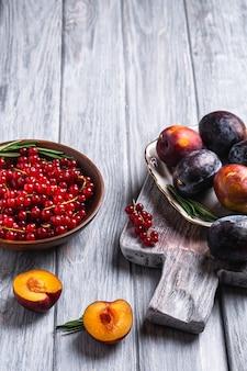 Свежие сладкие плоды сливы целиком и нарезанные в тарелке с листьями розмарина на старой разделочной доске с ягодами красной смородины в деревянной миске