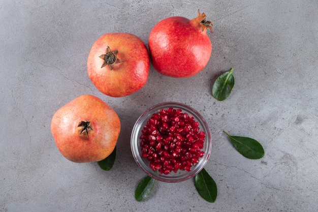 Fresh sweet pomegranates with leaves placed on stone table.