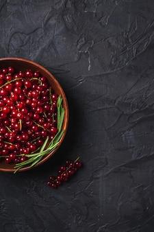 Свежие сладкие ягоды красной смородины с листьями розмарина в деревянной миске