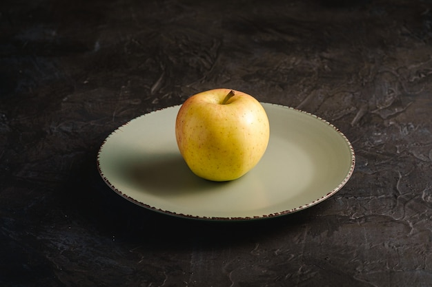 Fresh sweet single apple in grey plate on dark black textured background, angle view