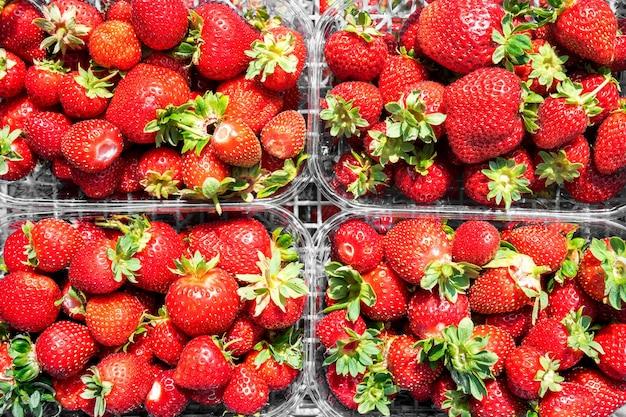 신선한 달콤한 딸기는 야채 시장에서 잘 익은 과일의 패턴과 질감을 판매합니다