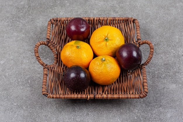 Fresh sweet tangerines with plums on a wicker basket