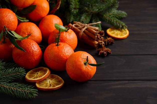 クリスマスのコンセプト、暗い木製の背景にスパイスと新鮮なタンジェリンclementines。