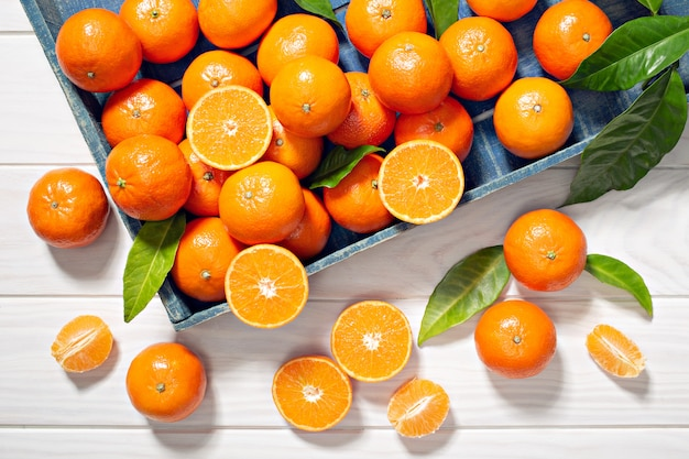Fresh tangerine fruits with leaves on wooden table