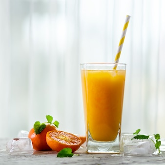 Fresh tangerine juice in glass. orange fruits with ice, mint. cold beverage for hot summer day.