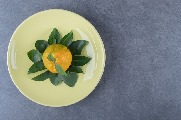 Fresh tangerine and leaves on yellow plate.