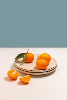 테이블에 금 테두리가있는 베이지 색 접시에 신선한 귤 또는 클레멘 틴 과일