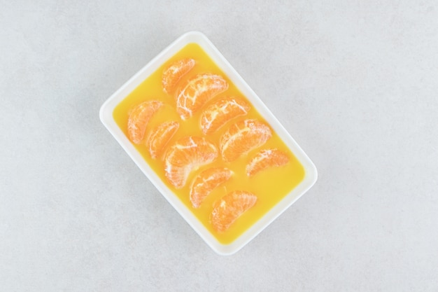 Fresh tangerine segments on white plate.