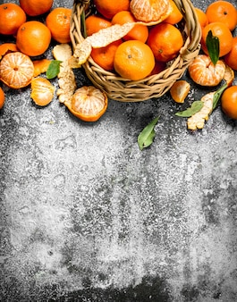 Fresh tangerines in a basket on rustic table.