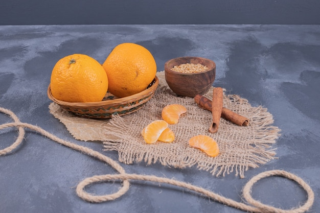 Mandarini freschi in ciotola e cannella sulla superficie blu.