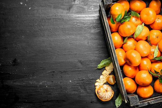 Fresh tangerines in a box on the black chalkboard