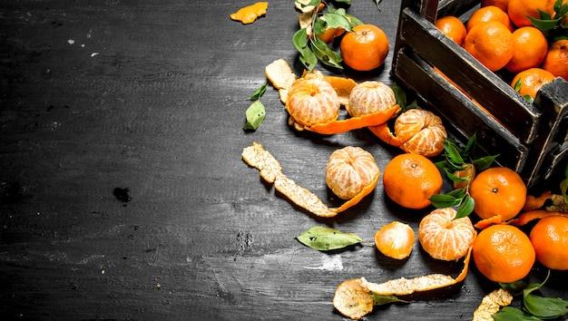 Fresh tangerines in a box on black chalkboard.