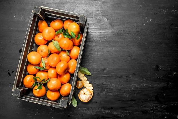 Fresh tangerines in a box. on the black chalkboard.
