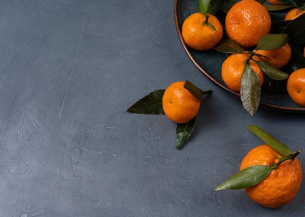 Свежие мандарины цитрусовые. плоды клементина с зелеными листьями с копией пространства