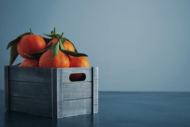Свежие мандарины в старой коробке с листьями, изолированными на деревенском синем столе и холодном фоне, вид сбоку крупным планом