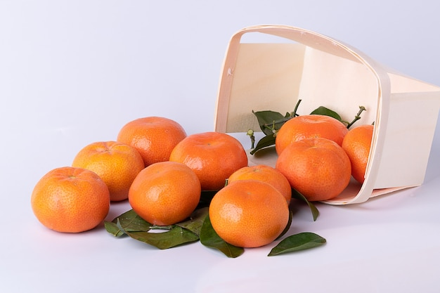 Fresh tangerines , mandarines, with leaves, in a wooden punnet- basket turned over with white surface.