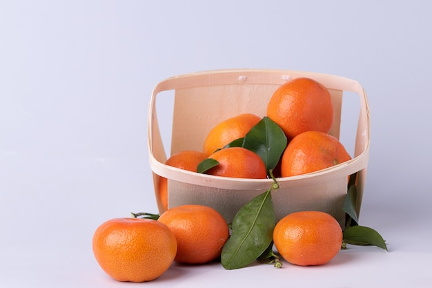 Fresh tangerines , mandarines, with leaves, in a wooden punnet- basket with white surface.