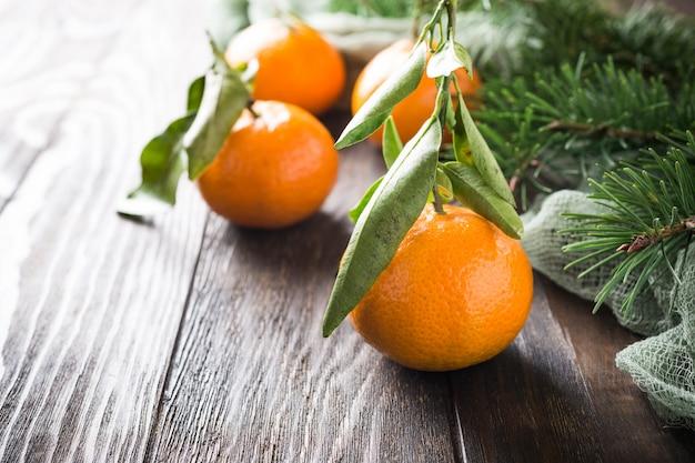 Свежие мандарины с листьями и спелых мандаринов на деревянный стол