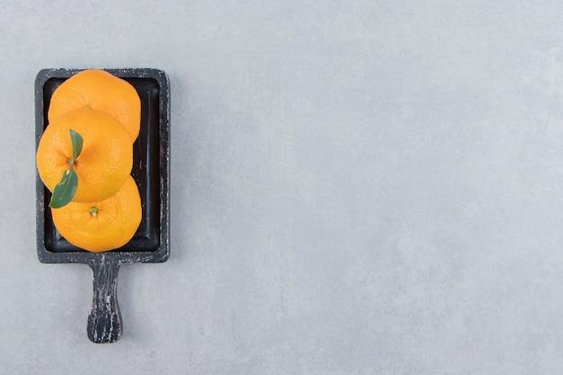 Mandarini freschi con foglie su tagliere nero.