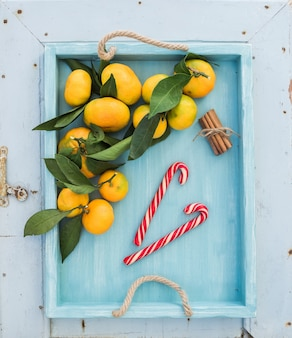 Fresh tangerines with leaves, cinnamon sticks and christmas candy canes in turquoise tray over blue rustic wooden backdrop, top view.