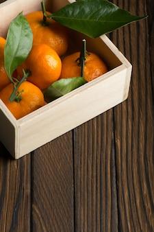 테이블에 나무 상자에 잎을 가진 신선한 귤