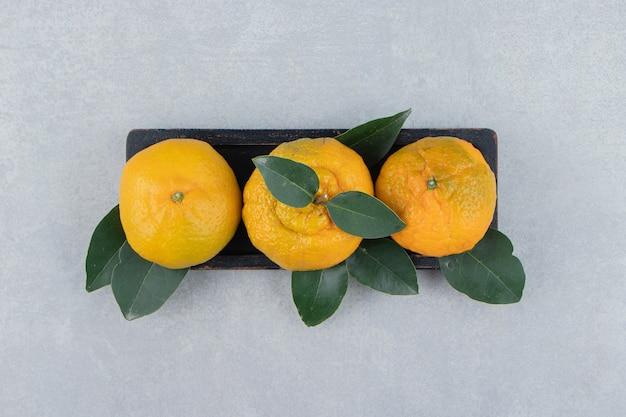 Свежие мандарины с листьями на черной тарелке.