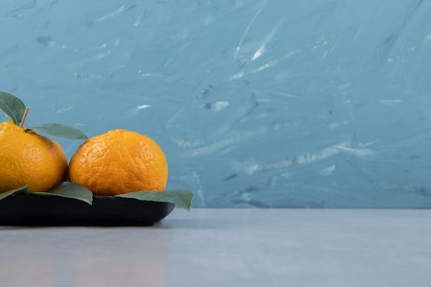Свежие мандарины с листьями на черной тарелке