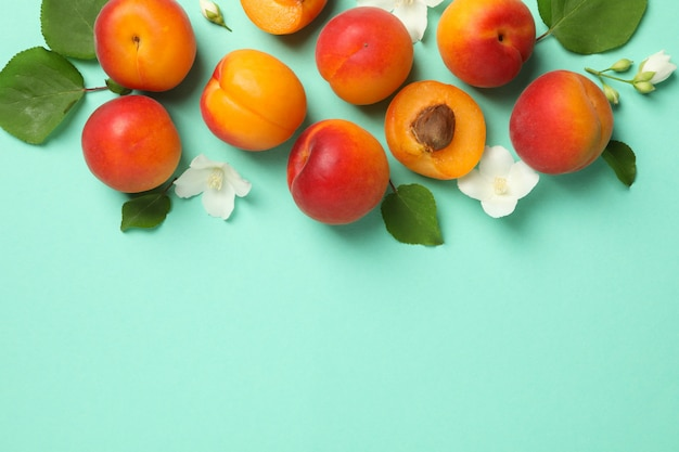 Fresh tasty apricots on mint background