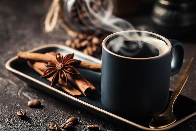Свежий вкусный черный эспрессо чашка горячего кофе с корицей, звездочками аниса и кофейными зернами на темном фоне