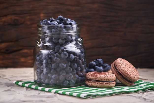 Fresh and tasty blueberry berries in a glass jar on a checkered napkin with sweet macaroons