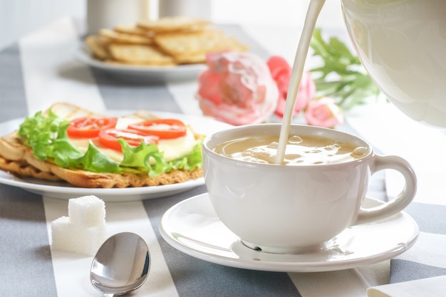 Fresh, tasty breakfast with a sandwich and tea on a light background.
