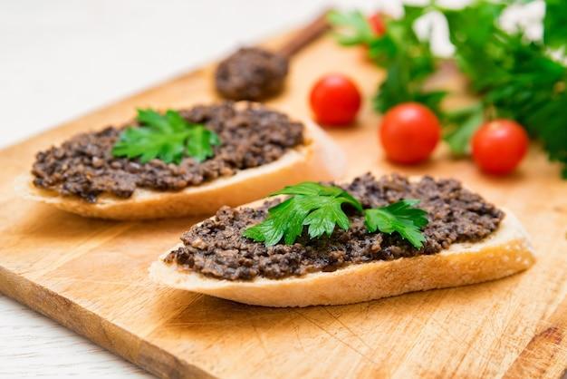 Свежая вкусная брускетта с трюфельным соусом, петрушкой и помидорами