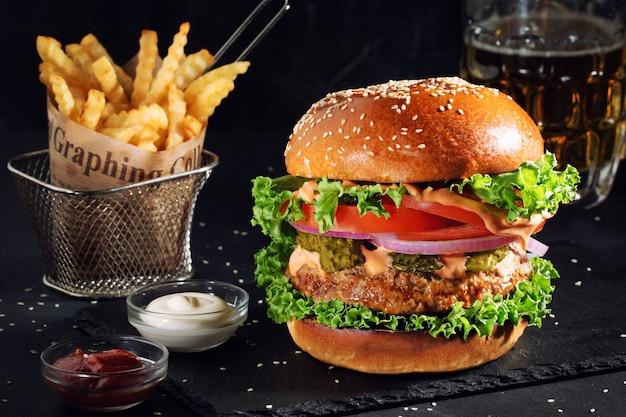 Свежий вкусный гамбургер и картофель на столе