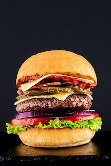 Fresh tasty burger on a black background.