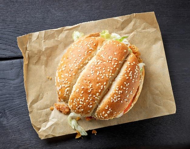 黒い木製のテーブル、上面図に新鮮なおいしいハンバーガー