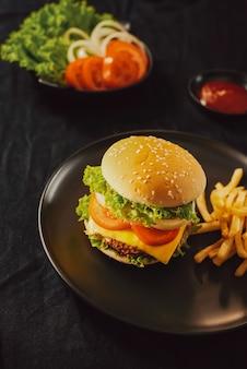 Свежий вкусный бургер на разделочной доске с картофелем фри, кетчупом и колой в стакане на черном фоне