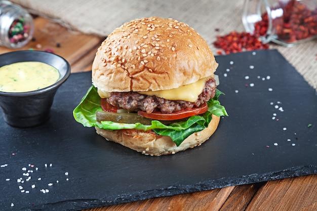 Свежий вкусный бургер с сыром, листьями салата, помидорами, огурцами на черном камне с соусом. американский фаст фуд. чизбургер с копией пространства на деревянных фоне. крупным планом, селективный фокус. продукты питания. гриль-меню