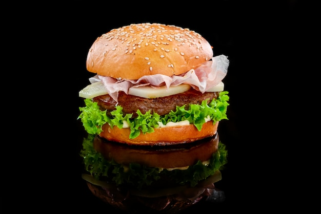 Fresh tasty burger with ham and pear on black surface