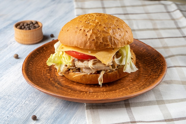 Fresh and tasty burger with roast beef, tomato, lettuce and cheese on blue wooden background. american traditional fastfood. food photo background.