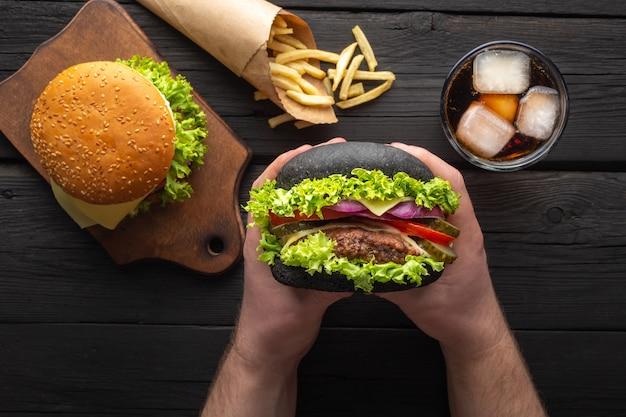 Свежие вкусные гамбургеры с картофелем фри, напиток на деревянном столе.